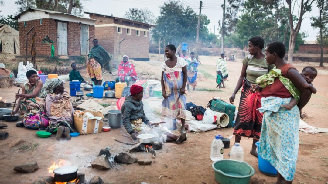 Schwangere Frauen und andere mit ihren Kindern an einem Hof außerhalb einer Klinik kochen auf dem Boden Abendessen
