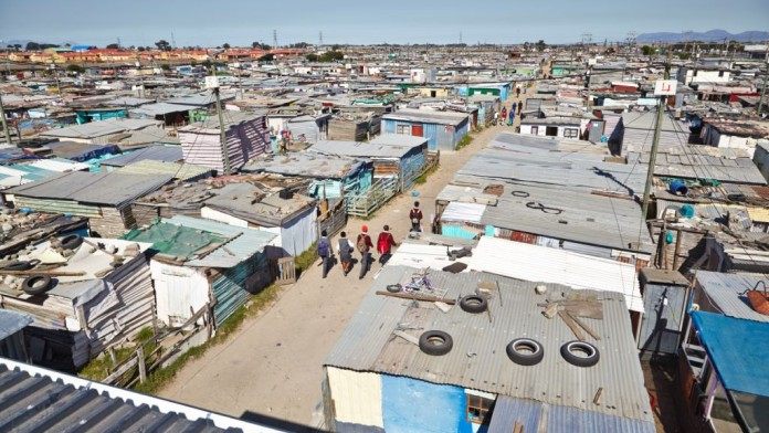 Schulkinder laufen durch einen Slum