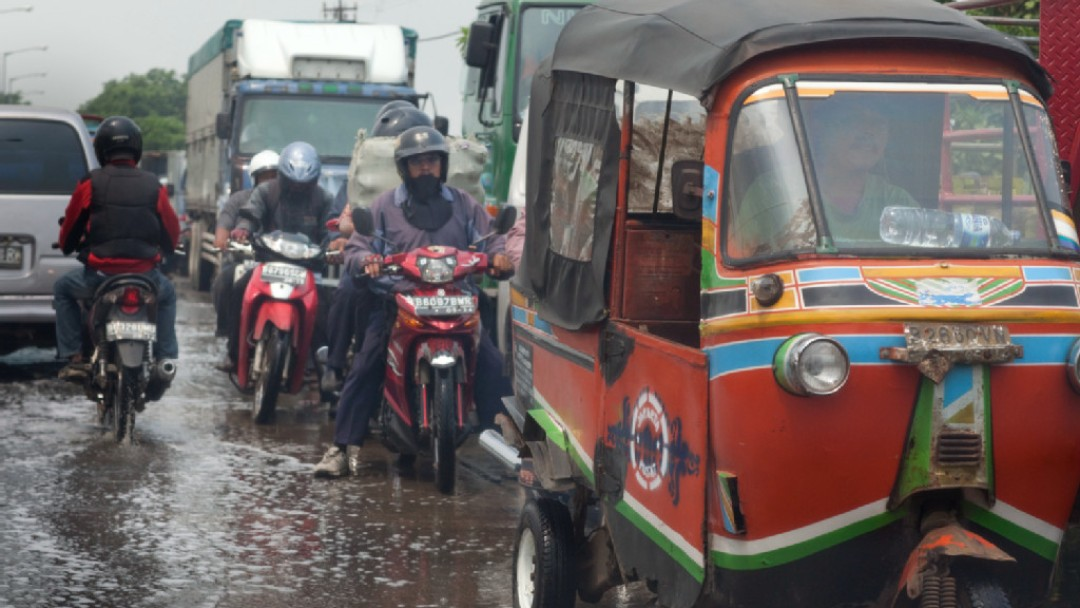 A Tuk-Tuk and several motorbikes are driving on a wet road in Asia.