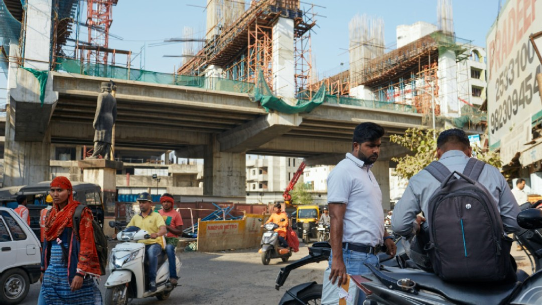 Construction of a metro, in the foreground people with mopeds.