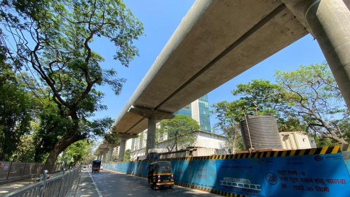 Part of the elevated metro system in Mumbai next to a road.