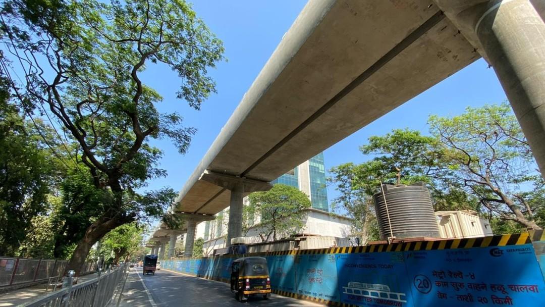 Ein Teil des hochgelagerten Metrosystems in Mumbai neben einer Straße.