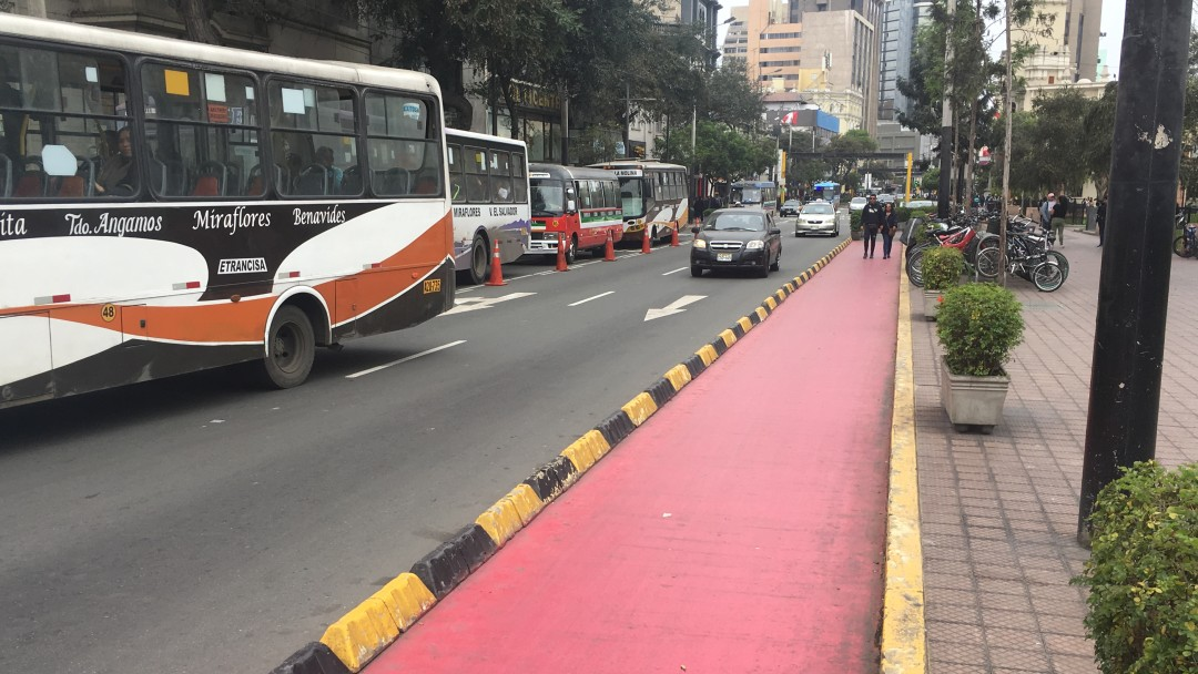 Red cycle path next to a busy road in Peru.