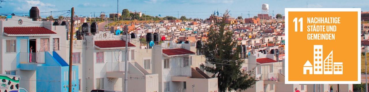 """Eine große, nachhaltige Wohnsiedlung, daneben das SDG11-Icon: """"Nachhaltige Städte und Gemeinden"""""""