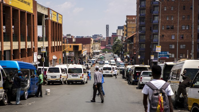 Pedestrians and cars on a street in Johannesburg.