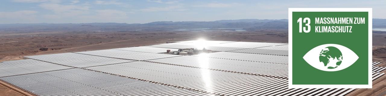 große Fotovoltailkanlage in karger Umgebung, welche stark von der Sonne angestrahlt wird. Am Rand ist das SDG 13 Icon: Maßnahmen zum Klimaschutz