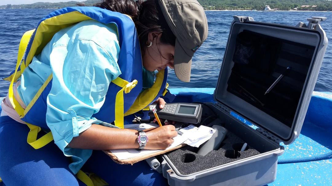 Eine Frau notiert sich Daten zur Sicherung der Wasserqualität