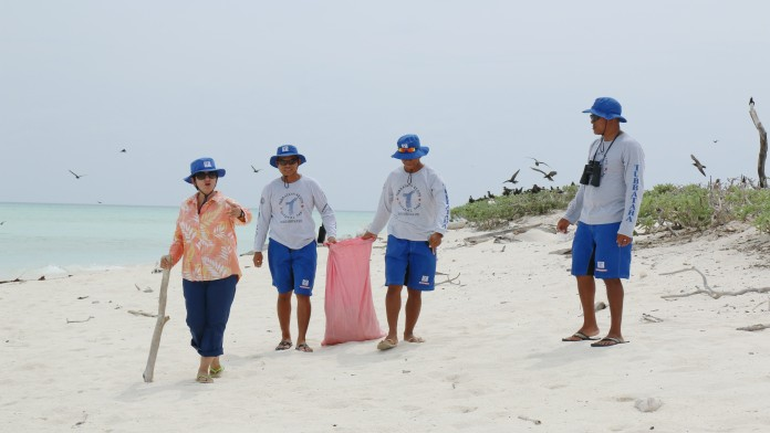 Angelique Songco, head of the Tubbataha Reefs Natural Park Department, and colleagues collecting litter on the beach