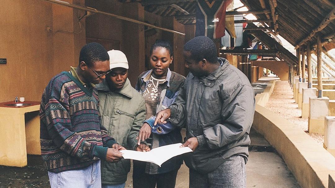 Studenten des South African Wildlife College schauen gemeinsam auf einen Plan