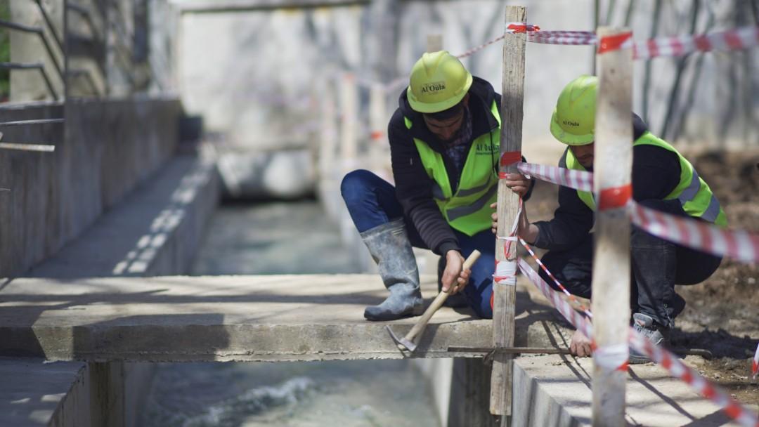 2 Studenten des WASH-Programms in Arbeitskleidung und -helm arbeiten an einer Baustelle