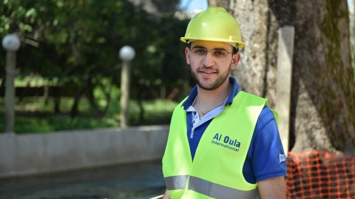Der 21-jährige libanesische Student Sarkis Farchakh des WASH-Programms mit Arbeitskleidung und -helm auf einer Baustelle