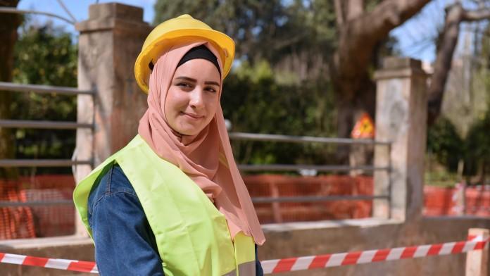 Die 21-jährige libanesische Studentin Rouya Malas mit Arbeitskleidung und -helm auf einer Baustelle