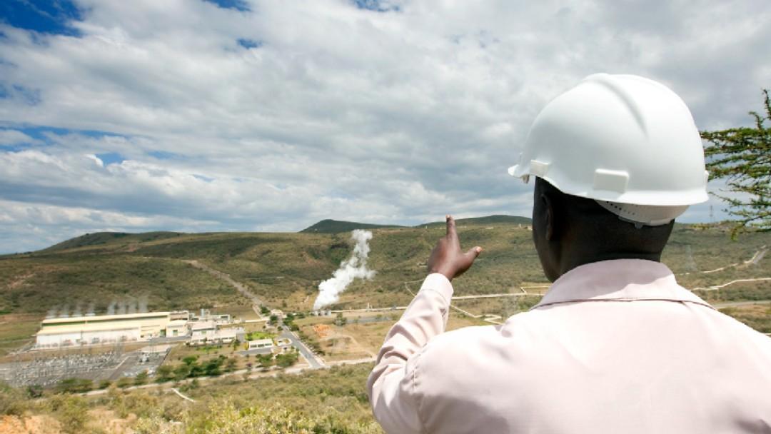 Ein Ingenieur erläutert die Außenanlage eines Geothermalwärmekraftwerks
