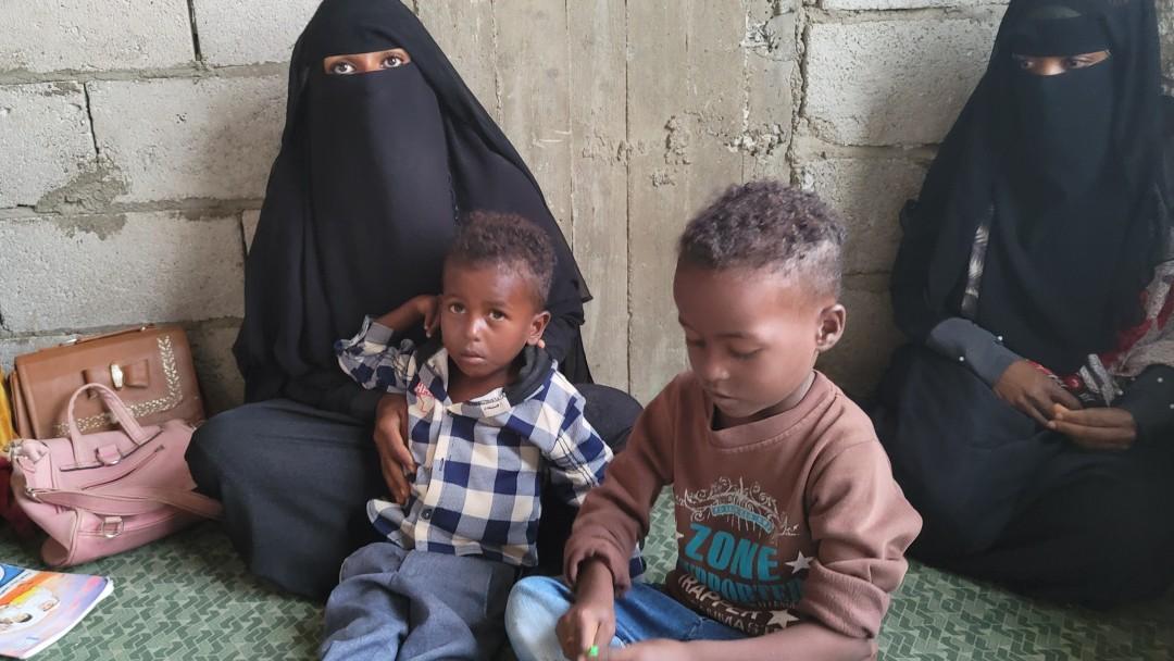 Frauen sitzen mit ihren Kindern im Klassenzimmer auf dem Boden
