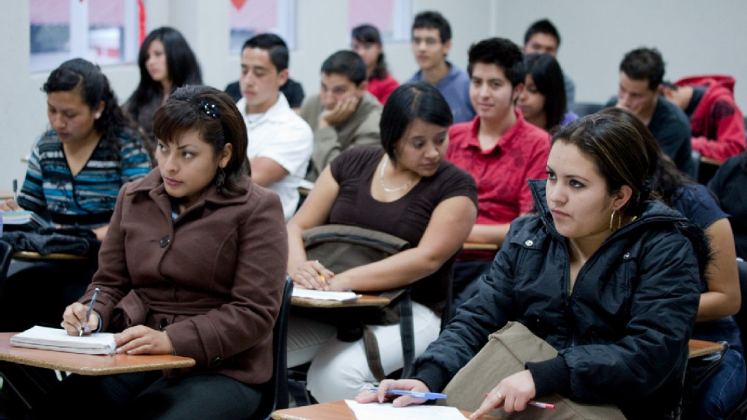 Guatemala: students sit in a classroom and write in their notebooks.