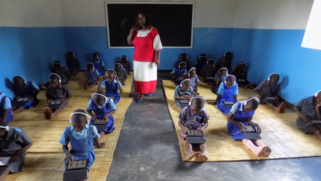 Malawi: Schüler sitzen im Klassenraum auf dem Boden mit Tablets auf ihren Schößen, auf denen sie, von ihrer Lehrerin beobachtet, Schulaufgaben lösen.