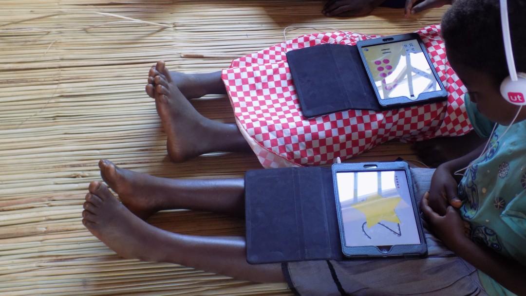Malawi: zwei Schülerinnen sitzen im Klassenraum auf dem Boden mit einem Tablet auf dem Schoß, auf dem sie Rechenaufgaben lösen.