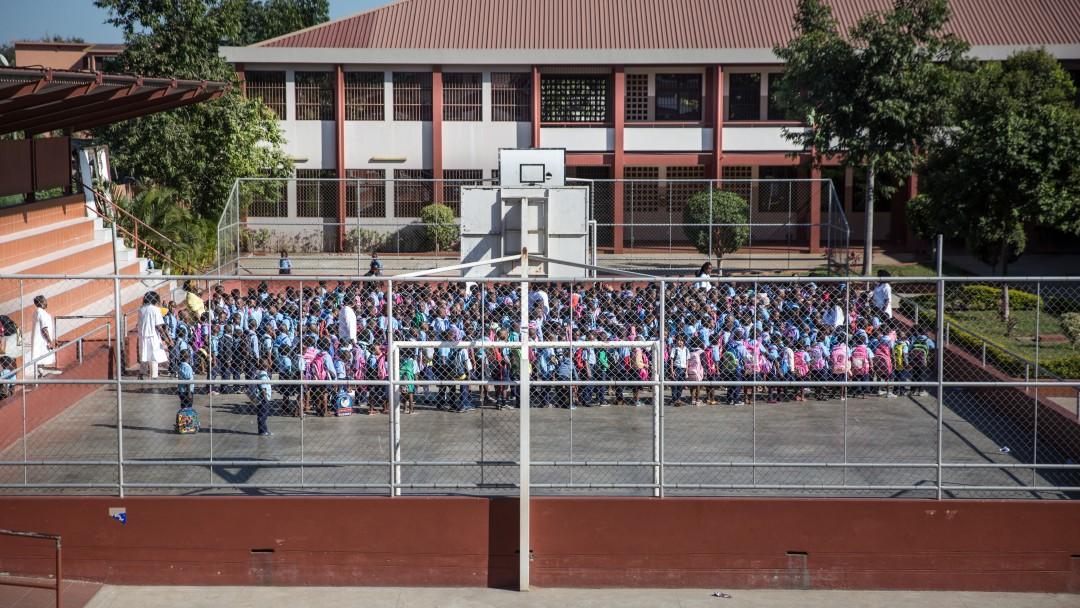 Grundschule in Maputo: drei Lehrerinnen versammeln die Schüler auf dem Sportplatz der Schule, im Hintergrund befindet sich das Schulgebäude.