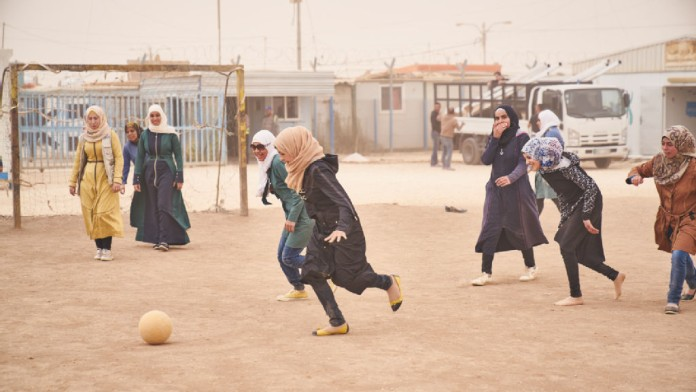 Girls playing on a soccer field at the UNICEF Makani Center for Education and Non-formal Education in the refugee camp in Jordan