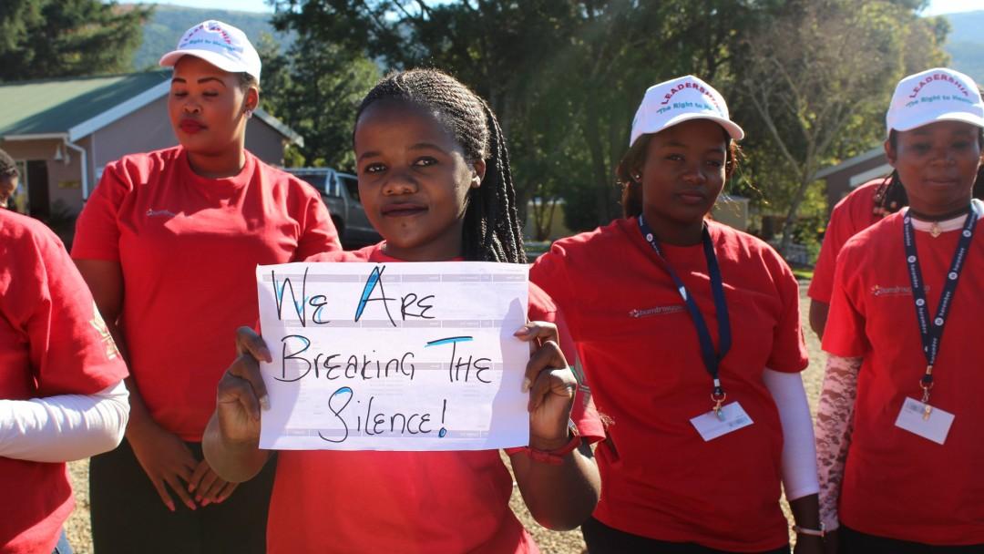 """Eine junge Frau hält ein Schild hoch: """"We are breaking the silence!"""""""