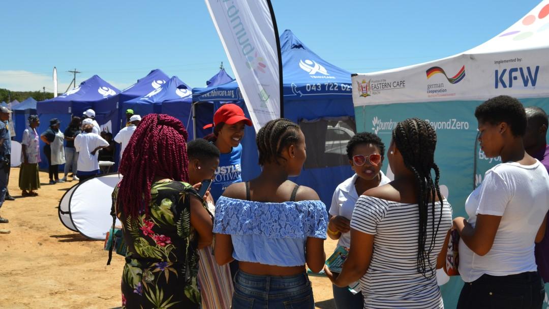 Junge Frauen stehen vor einem Info-Stand und unterhalten sich