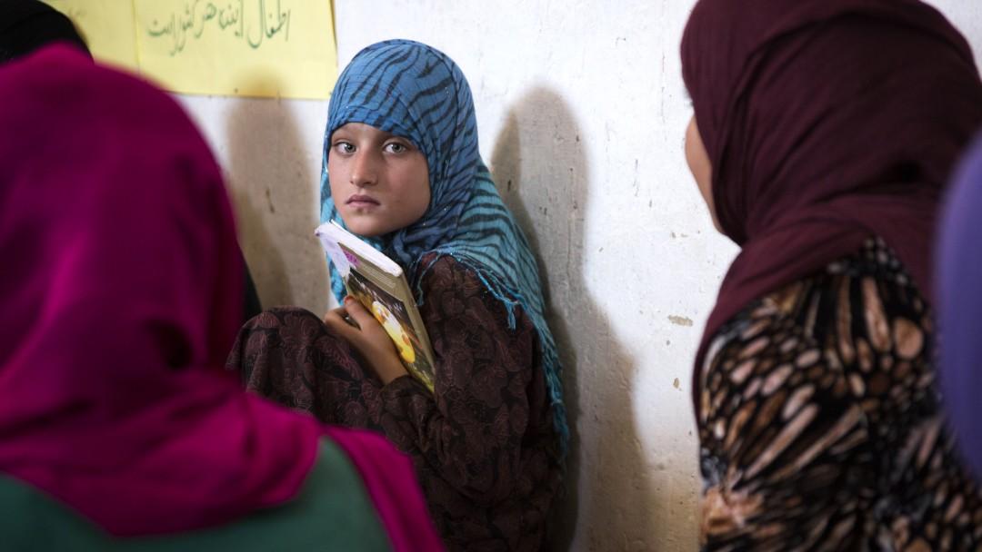 Eine junge Frau sitzt mit ihren Schulbüchern auf dem Boden eines Klassenzimmers