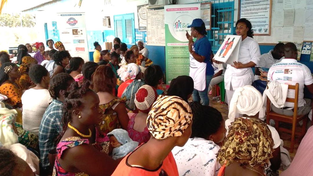 Eine Frau hält vor einer großen Gruppe einen Vortrag über Verhütung