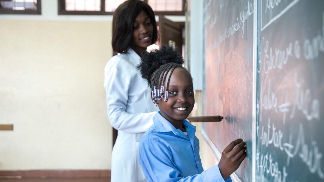 Ein Mädchen steht mit ihrer Lehrerin an der Tafel und schreibt etwas.