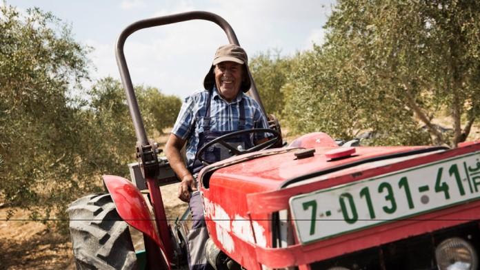 ein älterer Mann, der auf einem Traktor sitzt und lächelt