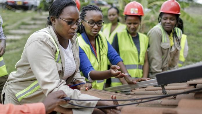 Afrikanische Arbeiterinnen mit Helmen arbeiten an einem Dach