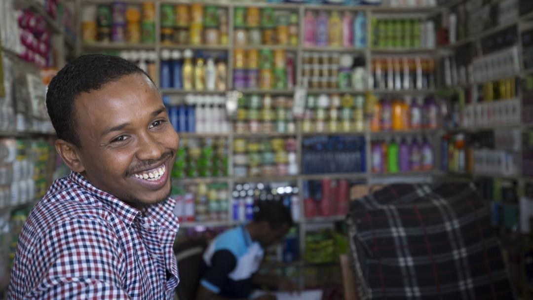 Liban Tahlil steht in einem kleinen Ladengeschäft im Flüchtlingslager Kakuma und lächelt in die Kamera.