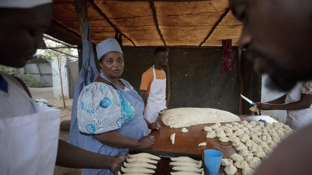 Eine Frau steht an einem Tisch und formt Teig zu Brot. Weitere Männer und Frauen arbeiten mit.