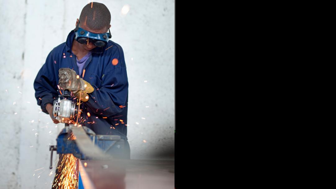 Ein junger afrikanischer Arbeiter mit Schutzbrille schleift eine Platte, sodass Funken sprühen