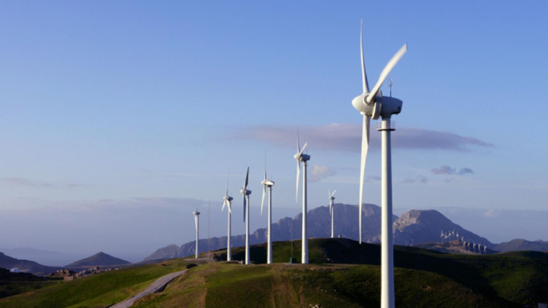 Seven wind turbines in the middle of hills. In the background there are more