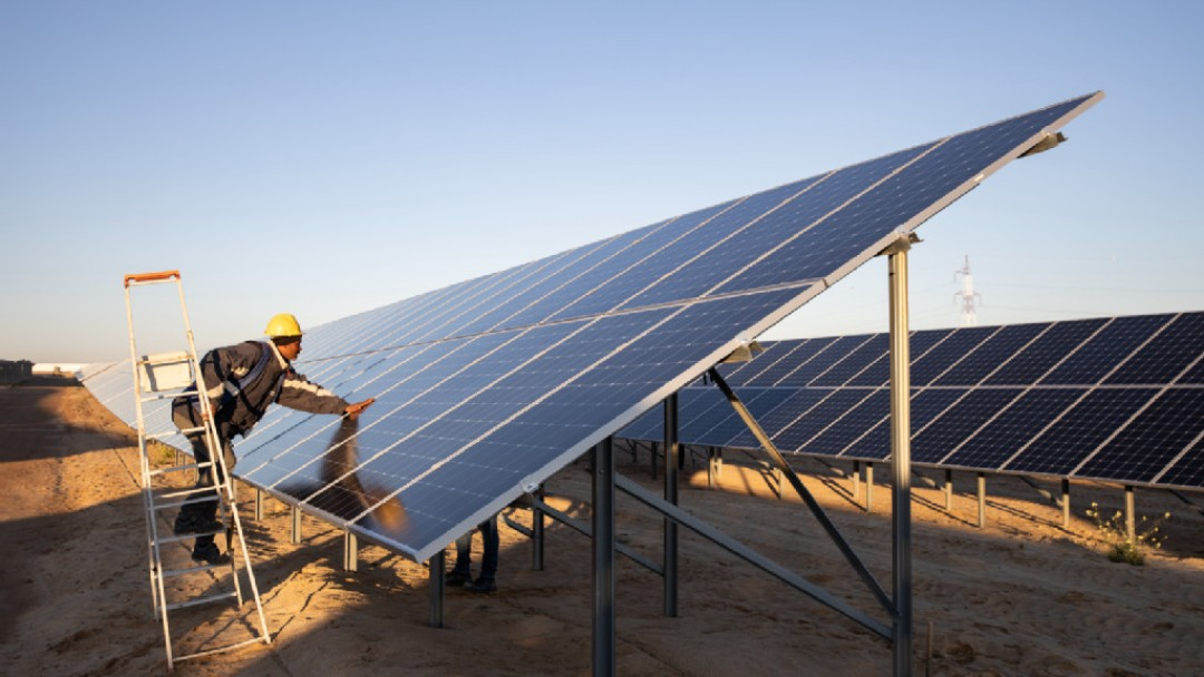 Worker stands on a ladder and leans over a solar panel to work on