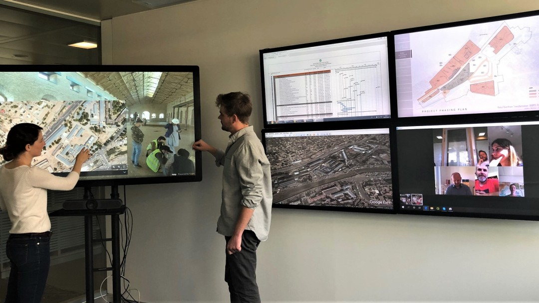 Room with several screens, on one of them two colleagues show pictures from a construction site, on the other one you see the floor plan, some statistics and other colleagues watching.