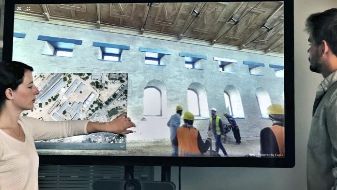 zwei Kollegen stehen vor einem Bildschirm auf dem sie auf eine Baustelle eines Gebäudes in Kabul schauen