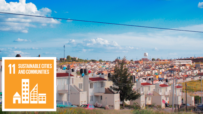 """A large, sustainable housing estate, next to the SDG11 icon: """"Sustainable cities and municipalities""""."""