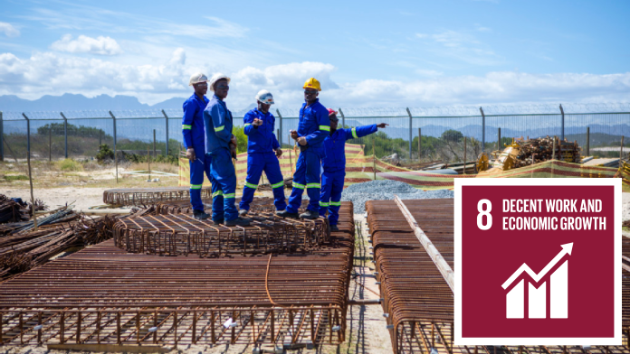 African construction workers on a building site, next to them SDG 8 icon: Decent work and economic growth