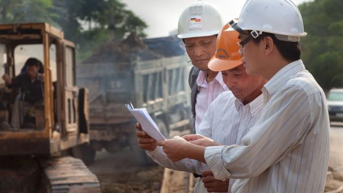 Asiatische Bauarbeiter und Ingenieure beugen sich über Karten.