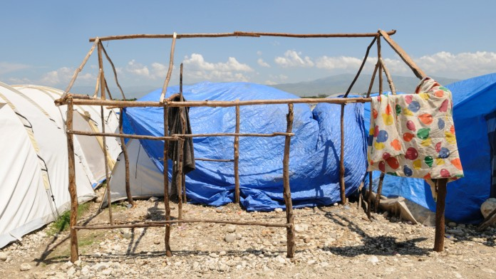 Ein aus Holzstäben errichtetes Zeltgerüst ohne Stoff. An der Seite hängt eine bunte Decke