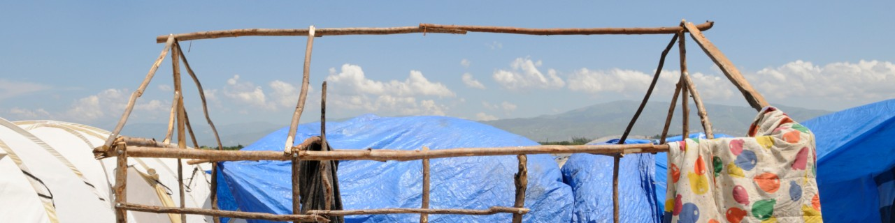 A tent construction out of wood without cloth amidst several refugee tents