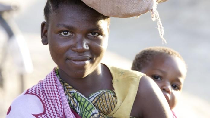 Frau mit Kind auf Rücken, trägt Waren auf dem Kopf
