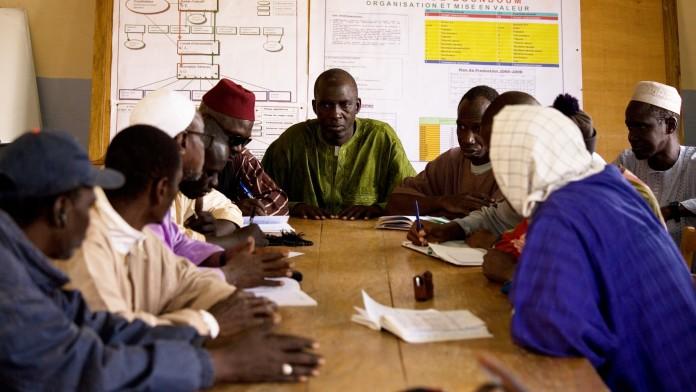 Zehn Männer sitzen um einen Tisch und diskutieren