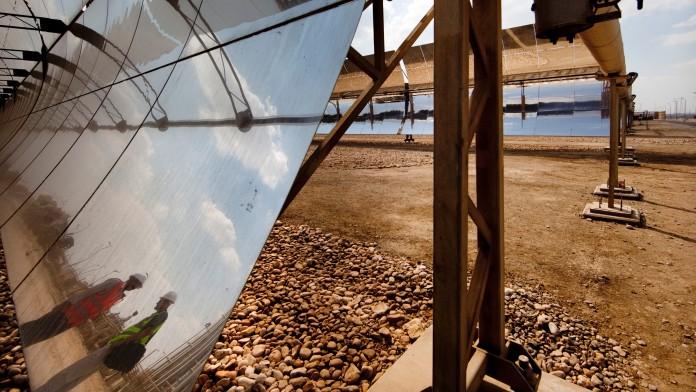 Solarpaneele in einem Sonnenkraftwerk, Arbeiter spiegeln sich in den Solarzellen