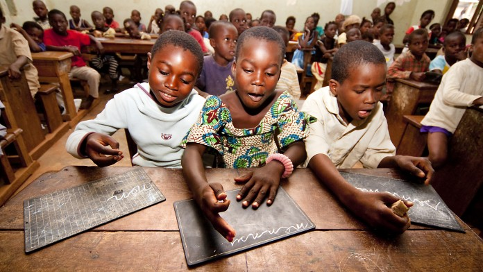 Three children in Africa write enthusiastically in their notebooks