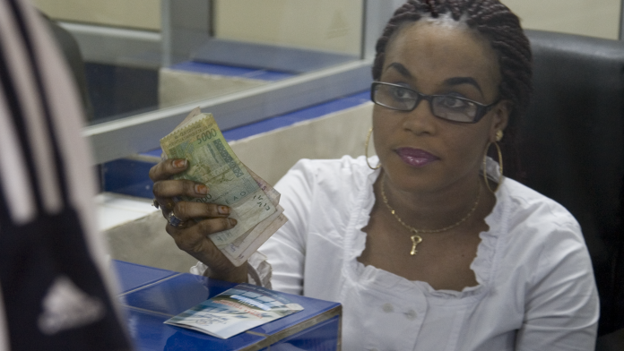 A woman in a bank holds money in her hand