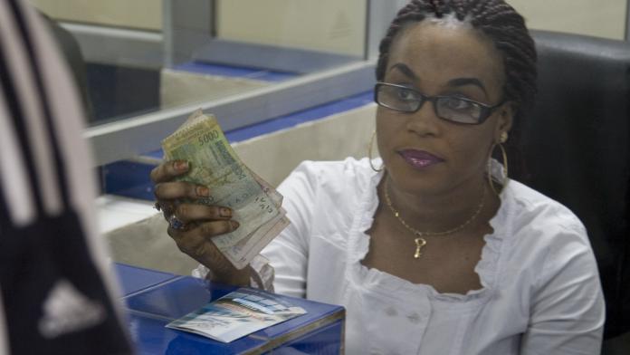 Eine Frau in einer Bank hält Geld in der Hand