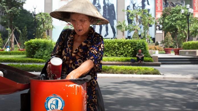 Eine Frau durchsucht einen Mülleimer